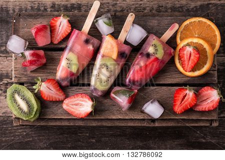 Healthy Whole Fruit Popsicles with Berries Kiwi strawberries on wooden vintage table