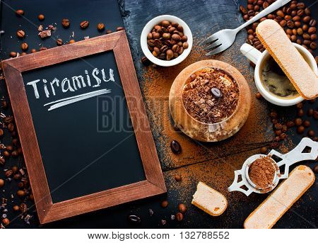 Tiramisu cake composition - traditional Italian dessert in glass cup of coffee cookies savoiardi coffee beans cocoa powder top view. Blanck space for text on chalkboard