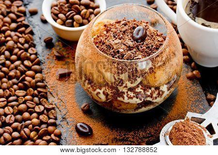 Tiramisu cake. Dessert with chocolate cocoa and coffee beans on black background. Traditional Italian cuisine selective focus