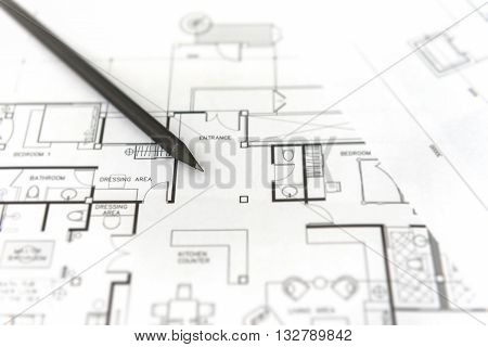 black pencil on architectural for construction drawings with roll of blueprint