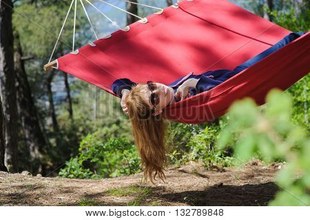 Happy Girl Relaxing In Hammock. Young smiling girl in glasses enjoy on red hammock in forest. Redhead woman with freckles smiles. Forest mountains in the background.