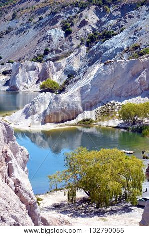 Blue Lake surrounded by white Quartz cliffs mined for gold in the 19th Century at St Bathans, on the Otago Rail Trail, New Zealand south Island
