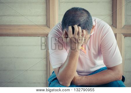 Anxious asian man feeling sadness and stress sitting on the chair process in vintage style