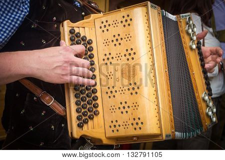 Traditional Bavarian accordion player playing folk music in Austria