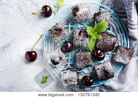 Homemade chocolate cherry brownie cake decorated with powdered sugar on blue rack on gray background. Healthy diet food concept. Copy space. Top view.