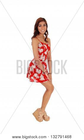 A lovely happy young woman standing in profile in a red dress smiling isolated for white background.