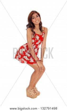 A gorgeous young woman standing in a red dress smiling putting out her bum isolated for white background.