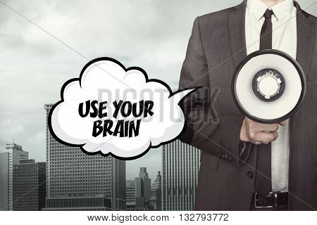 Use your brain text on speech bubble with businessman and megaphone on city background