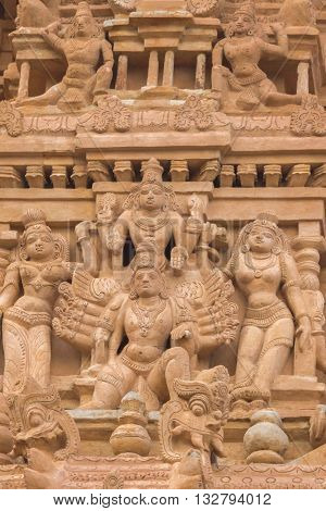 Chettinad India - October 16 2013: Detail of Shiva temple gopuram in Thirumayam. Multi-armed God surrounded by women.