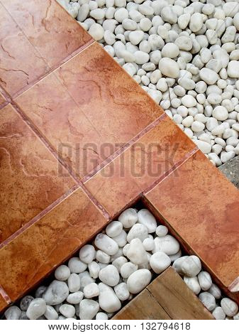 Landscaping combination of white pebbles and brown paving tiles.