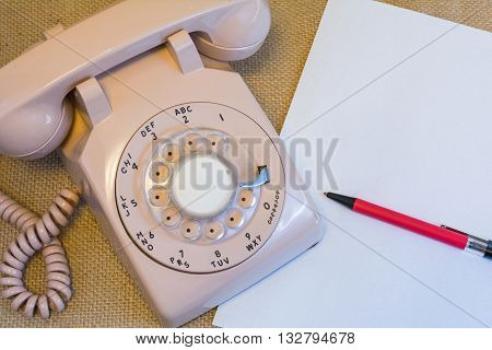 Vintage rotary telephone with blank white paper laying next to it
