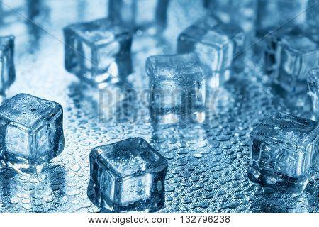 Many blue melting ice cubes on glass