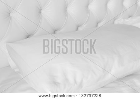 Close up white pillow on white luxury bed.