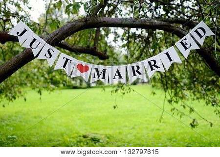 Beautiful wedding inscription 'just married' on the nature. Close-up beauty of colored placard. Bridal accessories. Female and male decoration for couple. Details for marriage