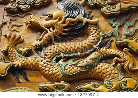 A ceramic glazed dragon on a wall within the forbidden city Beijing China.