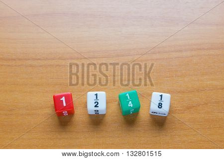 Four color fraction dices 1 1/2 1/4 and 1/8 on wooden table selective focus on dices