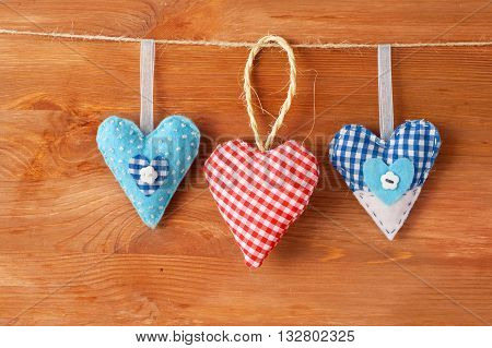 three stitched red hearts made of cloth hanging on a clothesline as a symbol for family