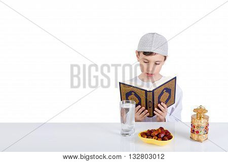 Young Muslim boy reading Quraan in Ramadan - sitting at a table with water dates Quran and Ramadan lantern