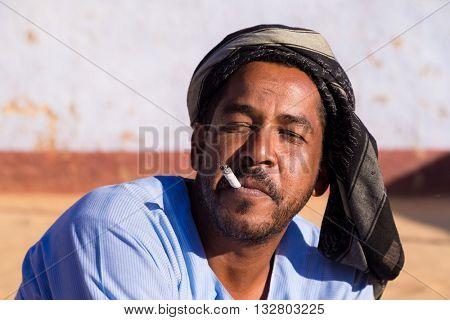 ASWAN, EGYPT - FEBRUARY 7, 2016: Portrait of Nubian man smoking cigarette.