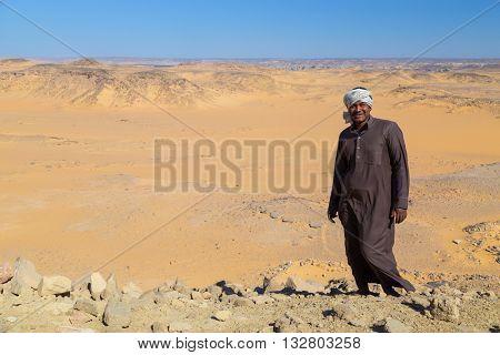 ASWAN, EGYPT - FEBRUARY 7, 2016: Nubian man wearing traditional clothing standing in sandy desert.