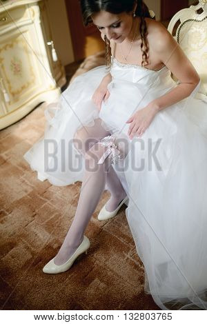 Beauty Bride In Dressing Gown Is Wearing Bridal Garter Indoors. Beautiful Model Girl In Colorful Wed