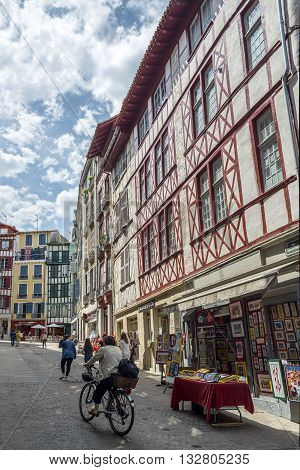 Bayonne France - May 21 2016: People in bike in Rue Argentiere street one of the most typical street of Bayonne. Aquitaine France.