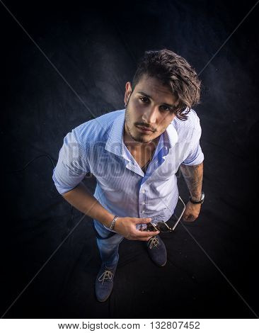 Portrait of brunette young man in light blue shirt and jeans, standing in studio shot from above perspective, against dark background. Full length photo