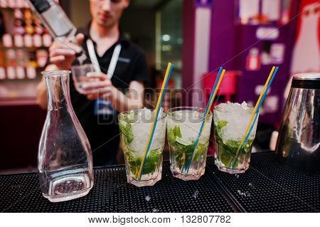Three Mojito Coctail Drink With Colored Tubes And Carafe Background Barman At The Bar