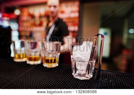 Glass With Ice And Tongs With Three Whiskey Glasses Background Barman