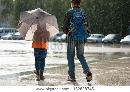 Two boys stand in the rain one of them is holding umbrella