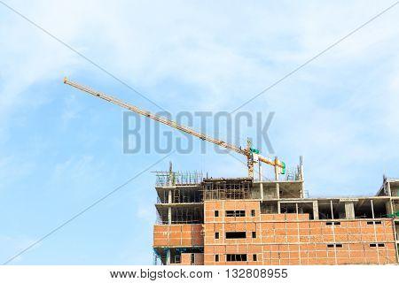 Building Crane And Construction Site Under Blue Sky
