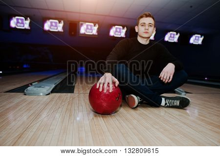 Young Man Holding A Bowling Ball Sitting Against Bowling Alleys With Ultraviolet Light. Focus On Bal