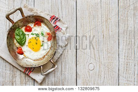 Fried egg with tomatoes and herbs n a old frying pan on wood