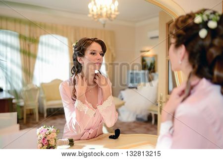 Beauty Bride In Dressing Gown Puts On Jewel Indoors. Beautiful Model Girl In Colorful Wedding Robe.