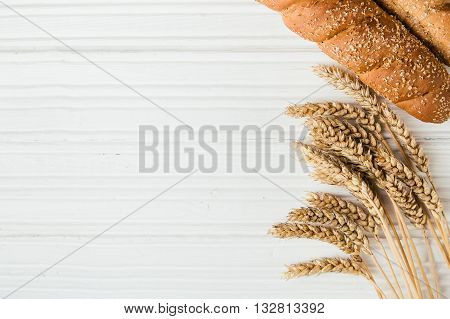 Golden ripe wheat and loaf of bread with bran on rustic white wooden background with copy space top view