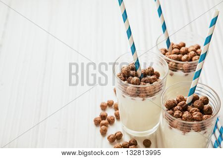 Chocolate corn balls with milk in glasses on white wooden background, side view, copy space