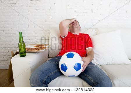 young soccer supporter man holding beer bottle watching football game on television sitting at home couch sad and disappointed for failure or defeat covering his face wearing team jersey