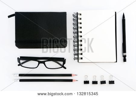 Top view of blank note book, eyeglasses and pencils