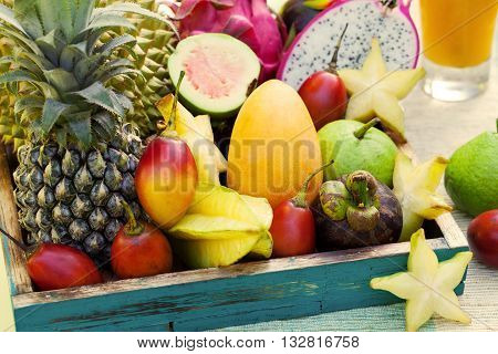 Assortment of tropical exotic fruits with smoothie and fresh juice on a tropical outdoor background