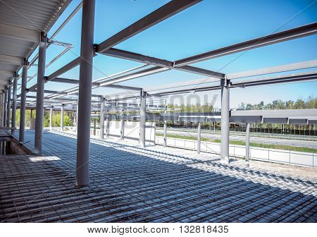 Building works. Construction works of new factory with channel girders, as a background