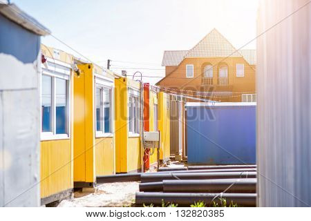Big and small. Yellow construction trailers made for workers to live while building works standing near a nice big house in a background