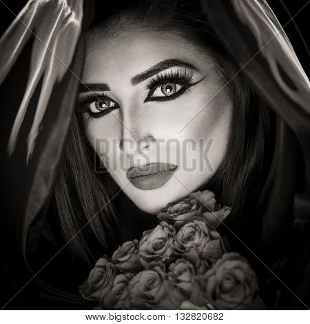 Fashion Portrait of a beautiful young woman holding a bouquet of red roses with a black cloak and veil