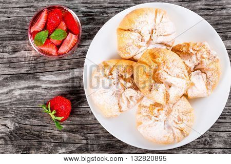 coconut and strawberry puff pastries on a white dish on an old wooden background with strawberry mint cold soft drink view from above