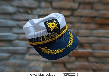 Levitating Venezia navy hat in front of blurred brick wall with zoom effect. Standard souvenir cap from Venice flying in front of brick wall with zoom effect.