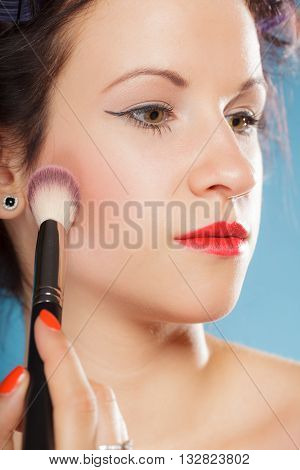 Cosmetic beauty procedures and makeover concept. Woman in hair curlers applying makeup blusher with brush. Girl gets blush on cheekbones on blue