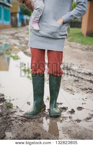 woman in rubber boots with a child standing in a puddle after a summer rain in the village