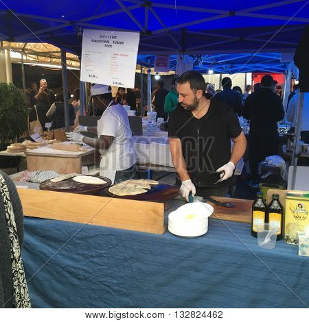 AUCKLANDJUNE 4: Turkish cook preparing gozleme a traditional savory Turkish flatbread and pastry dish at the La Cigale French Market in Auckland New Zealand on June 4 2016.