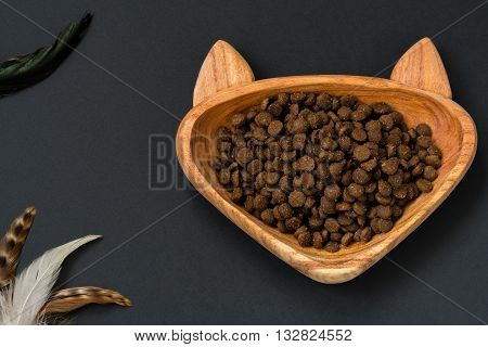Dry food for animals in wooden bowl - shape of cat and toy teaser with feathers.