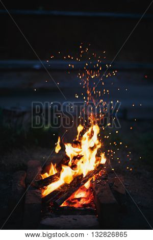 sparks fly from a campfire on a summer night