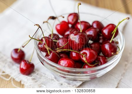 Fresh juicy sweet cherries in glass bowl. Rustic background with homespun napkin.